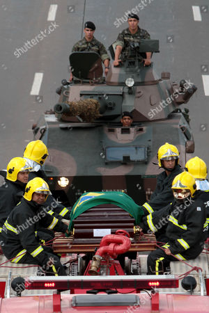 Military firefighters, front, sit on top of a fire truck by the coffin carrying the remains of Brazil's former Vice President Jose Alencar as soldiers follow behind to Planalto Palace in Brasilia, Brazil, . Alencar, who served two terms under President Luiz Inacio Lula da Silva, died Tuesday afternoon in a Sao Paulo hospital after fighting abdominal cancer since 1997. He was 79
