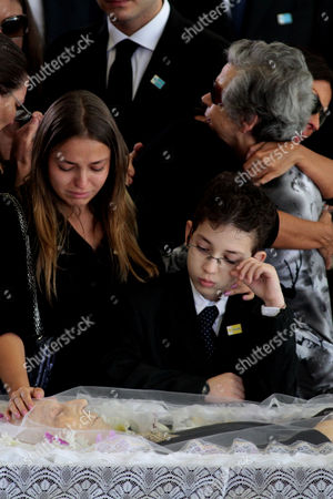 Unidentified family members mourn over the body of Brazil's former Vice President Jose Alencar during his wake at Planalto palace in Brasilia, Brazil, . Alencar, who served two terms under President Luiz Inacio Lula da Silva, died Tuesday afternoon in a Sao Paulo hospital after fighting abdominal cancer since 1997. He was 79