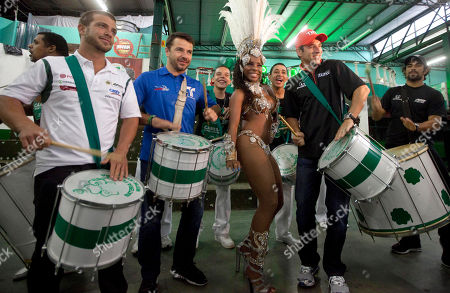 IndyCar drivers Raphael Matos, right, Helio Castroneves, second from right, both from Brazil, E.J. Viso, of Venezuela, left, and Oriol Servia, of Spain, second from left, accompanied by a dancer, play drums as they visit a samba school, in Sao Paulo, Brazil, . Brazil will host the 4th race of the 2011 IndyCar season on May 1