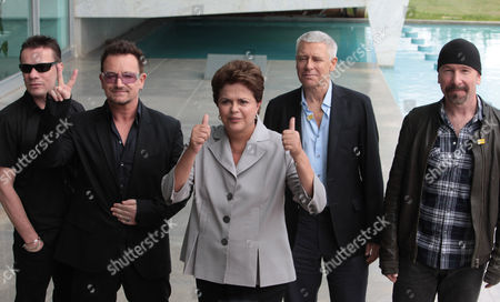 Stock Photo of Brazil's President Dilma Rousseff, center, flashes a thumbs-up as she receives U2 members, Larry Muller Jr., left, Bono, second left, Adam Clayton, second right, and The Edge, right, at the Alvorada Palace in Brasilia, Brazil