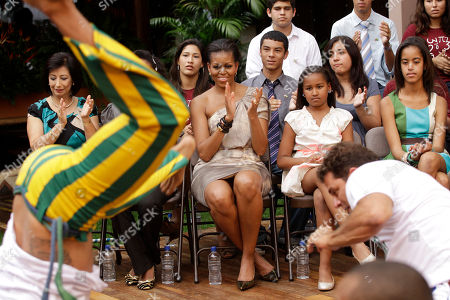 Michelle Obama, Natasha Obama U.S. first lady Michelle Obama, center, and her daughters Sasha, second from right, and Malia, far right, watch a Capoeira performance at Oca da Tribo restaurant in Brasilia, Brazil, . Michelle Obama and her two daughters attended a cultural performance with young Brazilians, many from disadvantaged backgrounds who have participated in a range of U.S. sponsored exchange and leadership development programs