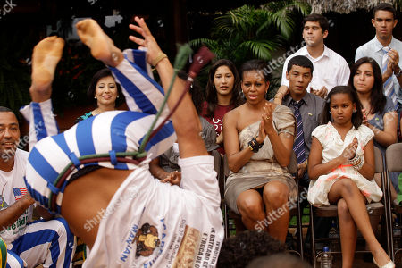 Michelle Obama, Natasha Obama U.S. first lady Michelle Obama, second from right in front row, and her daughter Sasha watch a Capoeira performance at Oca da Tribo restaurant in Brasilia, Brazil, . Michelle Obama and her two daughters Sasha and Malia attended a cultural performance with young Brazilians, many from disadvantaged backgrounds who have participated in a range of U.S. sponsored exchange and leadership development programs