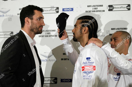 WBA boxing champion Britain's David Haye, center, is pulled away by his trainer Adam Booth, right, as he poses 'head to head' with WBO, IBO and IBF boxing champion Ukraine's Wladimir Klitschko, left, at the end of a news conference in London, . Klitschko and Haye are due to face each other for an open air heavyweight unification boxing fight at the Imtech soccer stadium in Hamburg, Germany on July 2, 2011