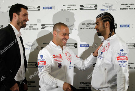WBA boxing champion Britain's David Haye, right, is pushed away by his trainer Adam Booth, center, as he poses 'head to head' with WBO, IBO and IBF boxing champion Ukraine's Wladimir Klitschko, left, at the end of a news conference in London, . Klitschko and Haye are due to face each other for an open air heavyweight unification boxing fight at the Imtech soccer stadium in Hamburg, Germany on July 2, 2011