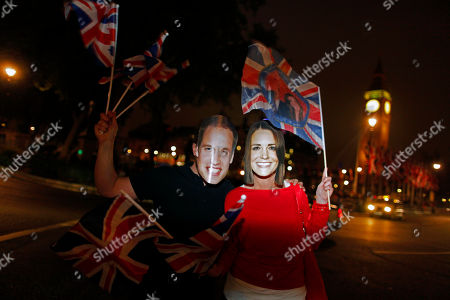 Graham Archer of Essex, left, and Kate Jackson of Brighton, right, cheer along the Royal Wedding route close to the Houses of Parliament in London late Thursday, April, 28, 2011
