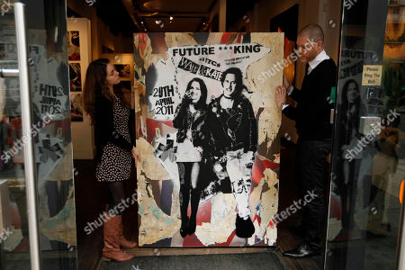 Opera Gallery director Jean-David Malet, right, and employee Florie-Anne Mondoloni, both from France, pose for photographs with a piece by street artist Rich Simmons portraying Britain's Prince William and his bride-to-be Kate Middleton as Sex Pistols punk band bassist Sid Vicious and his girlfriend Nancy Spungen in London, . Britain's Prince William and Kate Middleton are due to get married on April 29, 2011