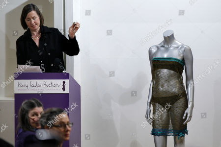 Stock Photo of The auctioneer hammers down to close the sale of the see-through knitted lace dress worn by Kate Middleton on display, right, during the 'Passion for Fashion' auction in central London, . The dress designed by Charlotte Todd was worn by Kate Middleton at the St. Andrew's University charity fashion show, is sold for 78,000 pounds (US$125,775 or 89,765