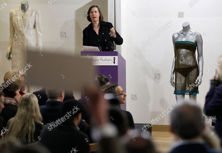 A bidder, representing an anonymous buyer, raises his buyer card, foreground, to bid, successfully, for the see-through knitted lace dress worn by Kate Middleton on display, right, during the 'Passion for Fashion' auction in central London, . The dress designed by Charlotte Todd was worn by Kate Middleton at the St. Andrew's University charity fashion show, is sold for 78,000 pounds (US$125,775 or 89,765