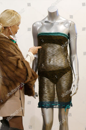 Stock Image of A visitor looks at a see-through knitted lace dress worn by Kate Middleton, on display before the start of the 'Passion for Fashion' auction in London, . The dress designed by Charlotte Todd was worn by Kate Middleton at the St. Andrew's University charity fashion show, and is due to be auctioned
