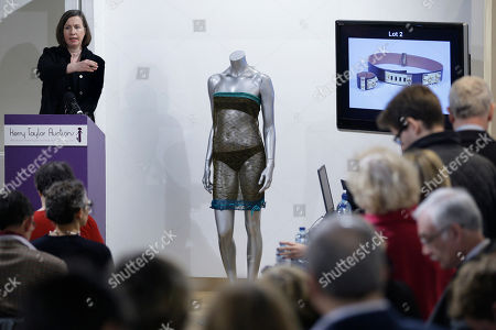 A see-through knitted lace dress worn by Kate Middleton stands on display in the middle of the room as the auctioneer sells a different lot during the 'Passion for Fashion' auction in central London, . The dress designed by Charlotte Todd was worn by Kate Middleton at the St. Andrew's University charity fashion show, is due to be auctioned