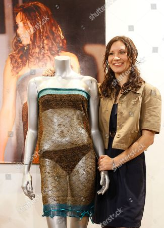 Charlotte Todd stands next to the dress she designed, and which was worn by Kate Middleton during a St Andrew's University charity fashion show in 2002, during a media event prior to its auction, in London, Wednesday, March, 16, 2011. The dress is expected to sell from between 8-10 thousand pounds (US $12,850-16,063, euro 9,200-11,500), when sold at auction Thursday. The photograph at rear shows Middleton wearing the dress at the charity fashion show