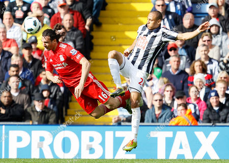 West Bromwich Albion's Peter Odemwingie, right, goes for the ball with Liverpool's Sotirios Kyrgiakos during their English Premier League soccer match at Hawthorns stadium in Birmingham, England, . (AP Photo/Alastair Grant) NO INTERNET/MOBILE USAGE WITHOUT FOOTBALL ASSOCIATION PREMIER LEAGUE(FAPL)LICENCE. CALL +44