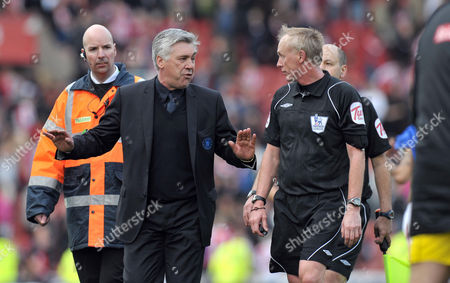 Chelsea manager Carlo Ancelotti, center left, speaks with referee Peter Walton after his team's 1-1 draw against Stoke City in their English Premier League soccer match at the Britannia Stadium, Stoke, England, . (AP Photo/Jon Super) NO INTERNET/MOBILE USAGE WITHOUT FOOTBALL ASSOCIATION PREMIER LEAGUE