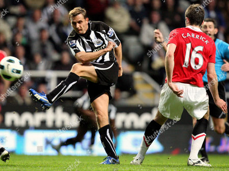 Newcastle United's Peter Lovenkrands, left, has a shot towards goal past Manchester United's Michael Carrick, right, during their English Premier League soccer match at St James' Park, Newcastle, England, . (AP Photo/Scott Heppell) NO INTERNET/MOBILE USAGE WITHOUT FOOTBALL ASSOCIATION PREMIER LEAGUE(FAPL)LICENCE. CALL +44