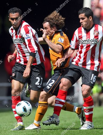 Stock Image of Sunderland's Ahmed Elmohamady, left, and Cristian Riveros, right, vies for the ball with Wolverhampton Wanderers' Stephen Hunt, center, during their English Premier League soccer match at the Stadium of Light, Sunderland, England, . (AP Photo/Scott Heppell) NO INTERNET/MOBILE USAGE WITHOUT FOOTBALL ASSOCIATION PREMIER LEAGUE(FAPL)LICENCE. CALL +44