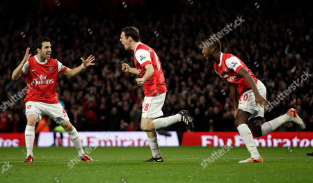 Arsenal's Sebastien Squillaci, center, celebrates his goal with Cesc Fabregas, left, and Johan Djourou during the English Premier League soccer match between Arsenal and Stoke City at the Emirates Stadium in London, . (AP Photo/Matt Dunham) NO INTERNET/MOBILE USAGE WITHOUT FOOTBALL ASSOCIATION PREMIER LEAGUE(FAPL)LICENCE. CALL +44
