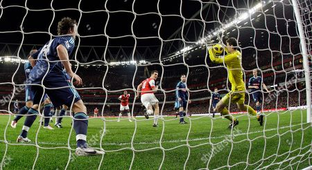 Arsenal's Sebastien Squillaci, center in red shirt, scores against Stoke City during the English Premier League soccer match at the Emirates Stadium in London, . (AP Photo/Matt Dunham) NO INTERNET/MOBILE USAGE WITHOUT FOOTBALL ASSOCIATION PREMIER LEAGUE(FAPL)LICENCE. CALL +44