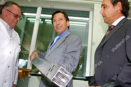 Energy Minister Laurence Golborne, center, holds a section used in the nuclear reactor RECH-1 as he stands with Hugo Torres, operator of RECH-1, left, and Jaime Gabriel Salas Kurte, executive director of Chile's nuclear energy commission, at the Nuclear Study Center in Santiago, Chile. Chile's President Sebastian Pinera is planning to sign a nuclear energy accord with the U.S. during President Barack Obama's upcoming visit to Santiago in March