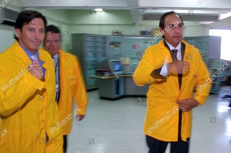 Energy Minister Laurence Golborne, left, CCHEN President Renato Agurto, center behind, and Executive Director of Chile's nuclear energy commission Jaime Gabriel Salas Kurte put on jackets before visiting the nuclear reactor RECH-1, at the Nuclear Study Center in Santiago, Chile