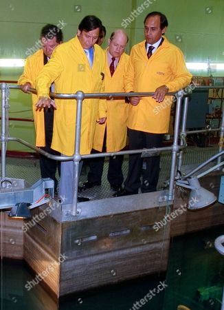 Energy Minister Laurence Golborne, second from left, CCHEN's advisor Julio Vergara, second from right, Executive Director of Chile's nuclear energy commission Jaime Gabriel Salas Kurte, right, and CCHEN President Renato Agurto, left, stand over the cooling system of nuclear reactor RECH-1 at the Nuclear Study Center in Santiago, Chile