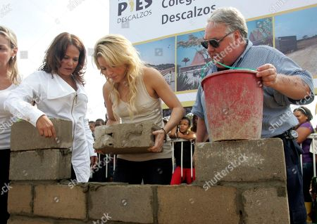 "Colombia's pop star Shakira, center, places a brick during a ceremony marking the start of construction on a school funded by her foundation ""Barefeet"" in the poor neighborhood of Loma del Peye in Cartagena, Colombia, . At right is Howard Buffett, son of Warren Buffett, and at left is Judith Pinedo, mayor of Cartagena"