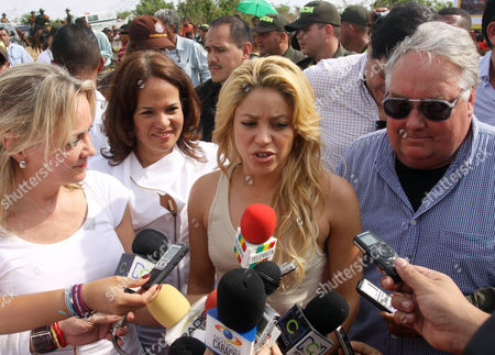 "Colombia's pop star Shakira speaks to the press after an event marking the start of construction on a school funded by her foundation ""Barefeet"" in the poor neighborhood of Loma del Peye in Cartagena, Colombia, . At right is Howard Buffett, son of Warren Buffett, and second from left is Judith Pinedo, mayor of Cartagena"