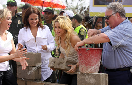 "Colombia's pop star Shakira, center, places a brick during a ceremony marking the start of construction on a school funded by her foundation ""Barefeet"" in the poor neighborhood of Loma del Peye in Cartagena, Colombia, . At right is Howard Buffett, son of Warren Buffett, and at far left is Judith Pinedo, mayor of Cartagena"