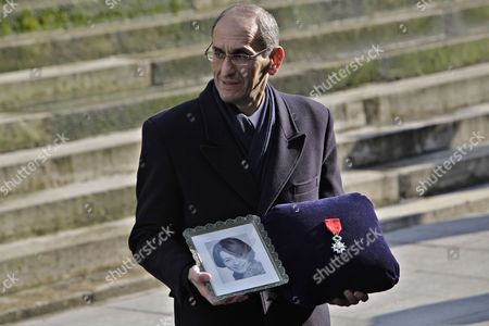 A funeral employee carries a photo and the Legion of Honor of French actress Annie Girardot, prior to the funeral ceremony held at the Saint Roch church in Paris, . Annie Girardot, the perky, gravelly-voiced actress who became one of France's most enduring and acclaimed modern stars, died on Monday. She was 79