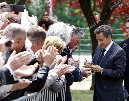 Nicolas Sarkozy French President Nicolas Sarkozy signs autographs as he arrives at a meeting on employment in Nancy, eastern France, . The Bild newspaper on Tuesday quoted Sarkozy's father Pal Sarkozy as confirming that his son and wife Carla Bruni-Sarkozy are expecting their first child together