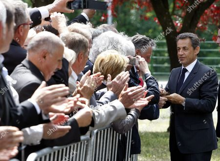 Nicolas Sarkozy French President Nicolas Sarkozy signs autographs as he arrives at a meeting on employment in Nancy, eastern France, .The Bild newspaper on Tuesday quoted Sarkozy's father Pal Sarkozy as confirming that his son and wife Carla Bruni-Sarkozy are expecting their first child together