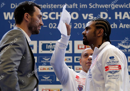 Wladimir Klitschko, David Haye Haye's coach Adam Booth, center, stops a three minutes face to face between British WBA box champion David Haye, right, and IBF and WBO box champion Wladimir Klitschko, left, from Ukraine during a news conference at the soccer stadium in Hamburg, Germany, . Klitschko and Haye will face each other for a open air heavy weight unification fight at the Imtech soccer stadium in Hamburg on July 2, 2011