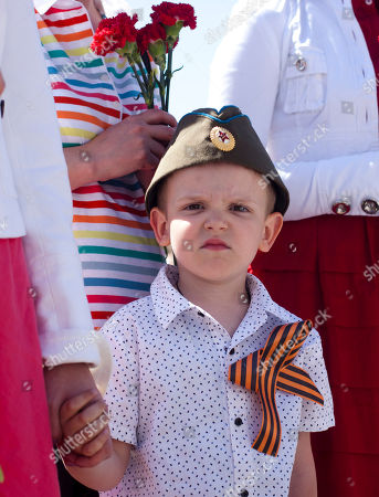 5 year-old Russian boy Olek wears a Red Army cap as he waits to lay down flowers during a ceremony that commemorates the 1945 defeat of Nazi Germany at the Soviet military memorial in central Berlin, Germany