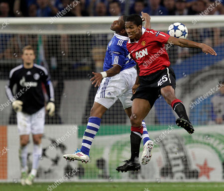 Schalke's Hans Sarpei, left, and Manchester's Antonio Valencia, right, challenge for the ball during the first leg Champions League semi final soccer match between FC Schalke 04 and Manchester United in Gelsenkirchen, Germany