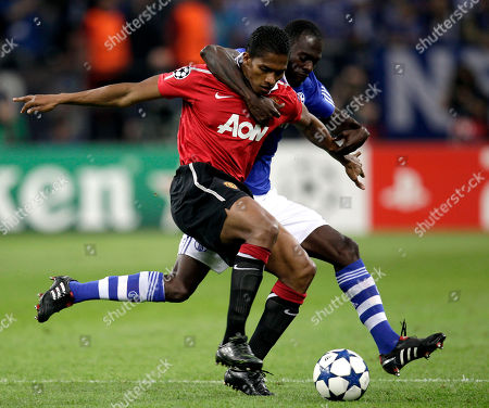 Schalke's Hans Sarpei, rear, and Manchester's Antonio Valencia, front, challenge for the ball during the first leg Champions League semi final soccer match between FC Schalke 04 and Manchester United in Gelsenkirchen, Germany