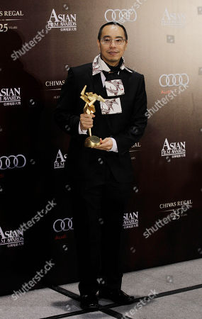"Apichatpong Weerasethakul Thailand director Apichatpong Weerasethakul poses with the trophy after winning the best film for the movie ""Uncle Boonmee Who Can Recall His Past Lives"" at the Asian Film Awards in Hong Kong"