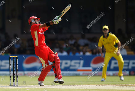Canada's John Davison, left, gets out to a ball from Australia's Brett Lee during a Cricket World Cup match between Australia and Canada in Bangalore, India