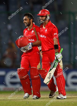 Canadian cricket team captain Ashish Bagai, left, and teammate John Davison walk with smiles on their faces after wnning their cricket world cup match against Kenya in New Delhi, India