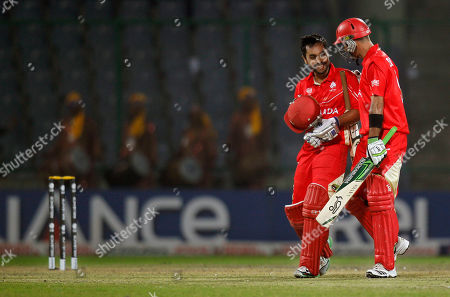 Canadian cricket team captain Ashish Bagai, left, and teammate John Davison walk with smiles on their faces after winning their cricket world cup match against Kenya in New Delhi, India