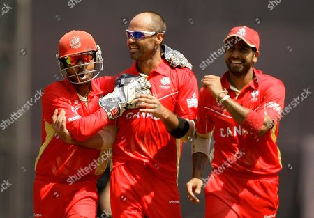 Ashish Bagai, John Davison, Zubin Surkari Canada's captain Ashish Bagai, left, John Davison, center and Zubin Surkari celebrates after the wicket of New Zealand's Jesse Ryder during the Cricket World Cup match against New Zealand in Mumbai, India