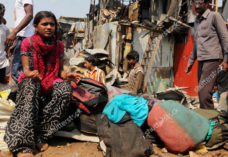 """Rubina Ali Slumdog Millionaire"""" child star Rubina Ali sits outside her house with her belongings at a slum in Mumbai, India, . Ali said Saturday that her home had burned down in a fire that raged through a crowded slum in the Indian city of Mumbai"""