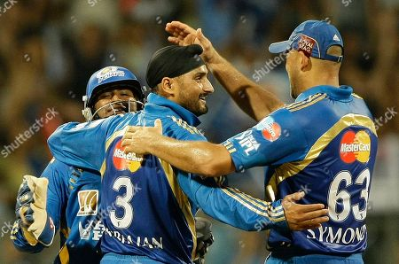 Mumbai Indians' Harbhajan Singh, center, and Andrew Symonds, right, celebrate the dismissal of Chennai Super Kings' Suresh Raina during the Indian Premier League (IPL) cricket match in Mumbai, India