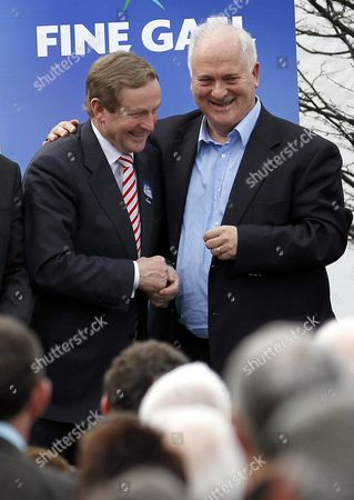Fine Gael leader Enda Kenny, left, is welcomed to the stage by former Irish Prime Minister John Bruton, right, after addressing supporters in his home town of Castlebar, County Mayo, Ireland, . Kenny was canvassing ahead of Friday's Irish general election were he widely tipped to be the next Irish Prime Minister