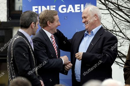 Fine Gael leader Enda Kenny, centre, is welcomed to the stage by former Irish Prime Minister John Bruton, right, after addressing supporters in his home town of Castlebar, County Mayo, Ireland, . Kenny was canvassing ahead of Friday's Irish general election were he widely tipped to be the next Irish Prime Minister