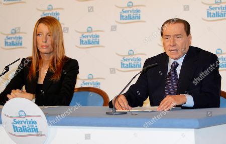 """Italian Prime Minister Silvio Berlusconi and Tourism Minister Michela Vittoria Brambilla attend a meeting in downtown Milan, Italy, . Premier Silvio Berlusconi went back on trial Monday for alleged tax fraud, the first of several court cases to resume after Italy's Constitutional Court watered down an immunity bill sparing the premier from trial. Prosecutors say Berlusconi's Mediaset media empire purchased TV rights for U.S. movies through two """"offshore"""" companies and falsely declared the costs to reduce the tax bill. Berlusconi, who wasn't in court Monday, has denied the allegations"""