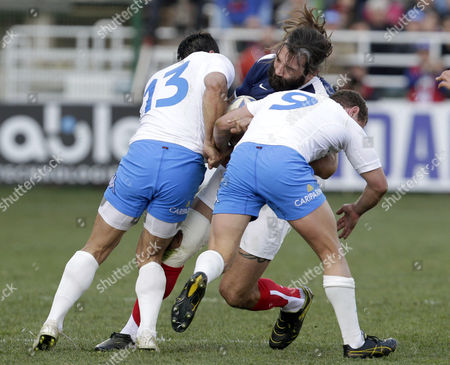 France's Sebastien Chabal, center, is tackled by Italy's Gonzalo Canale, left, and Fabio Semenzato during their six nations international rugby union match between Italy and France, in Rome