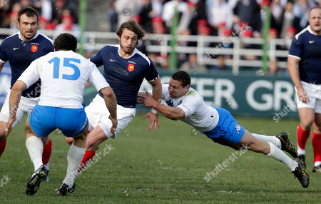 France's Maxim Medard, center, is tackled by Italy's Andrea Masi, left, and Fabio Semenzato during a six nations international rugby union match between Italy and France, in Rome