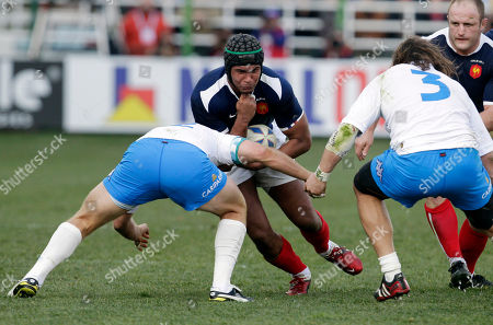 France's Thierry Dusatoir, center, is tackled by Italy's Gonzalo Garcia, left, and Martin Castrogiovanni during a six nations international rugby union match between Italy and France, in Rome
