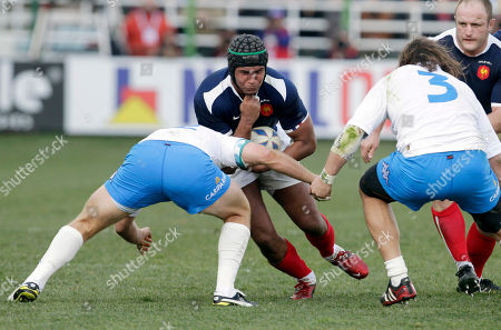 France's Thierry Dusatoir, center, is tackled by Italy's Gonzalo Garcia, left, and Martin Castrogiovanni during their six nations international rugby union match, in Rome