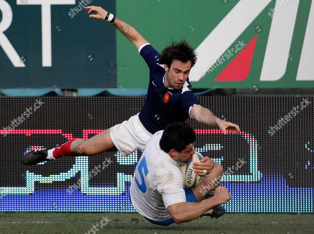 Italy's Andrea Masi, right, scores as France's Thierry Dusatoir tries to tackle him during a six nations international rugby union match in Rome