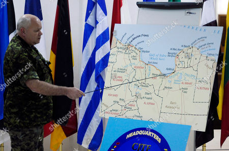 """NATO commander of the international military operation in Libya, Lt. Gen. Charles Bouchard, points at a map of Libya as he meets journalists at NATO headquarters, in Bagnoli, Naples, Italy, . Bouchard said NATO wasn't targeting Libyan leader Moammar Gadhafi when it bombed the presidential compound in Tripoli, saying it was trying instead to set the stage for diplomacy. He said the complex is """"a military compound in which there are various houses and residences ... and various military command and control nodes throughout"""